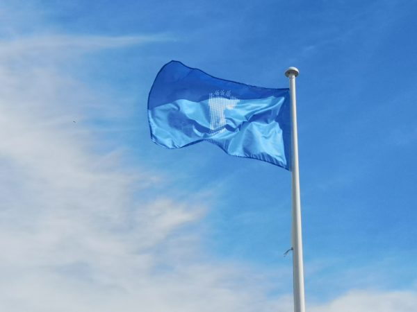 [Image Description: A blue flag with an image of a footprint in the centre. The flag is on a white pole against a backdrop of a bright blue sky!]