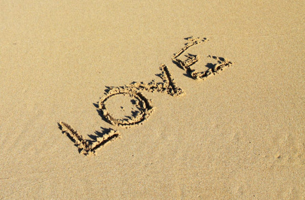 An image of the word 'Love' written in the Sand